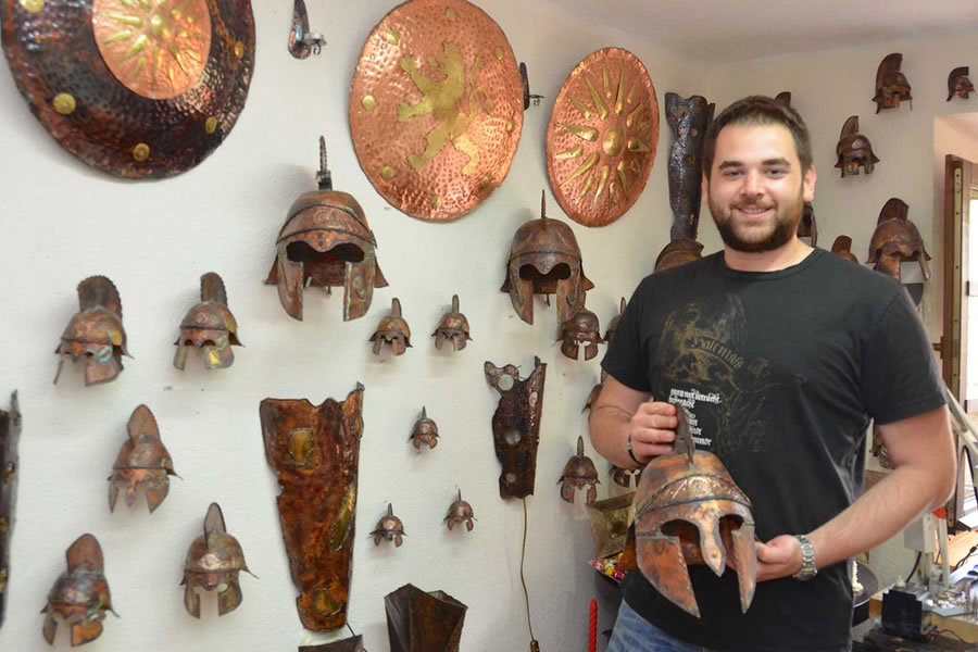A man, working in a souvenir jewelry shop in Ohrid, Macedonia, holds a reproduction warriors mask, fashioned after those worn in Ancient Macedonia.