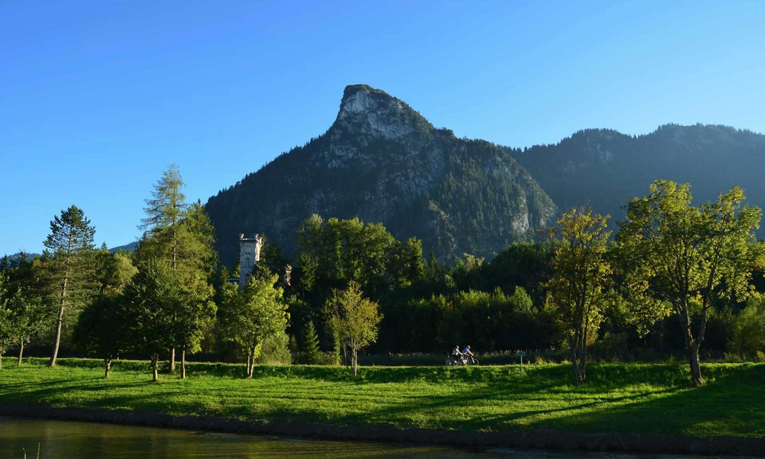 A pair of bicyclists ride on a pedestrian lane, in the shadows of Mount Kofel, a mountain peak in Oberammergau, Germany.