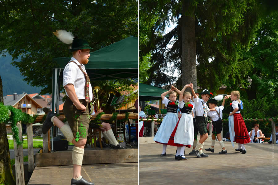 An adult, wearing a traditional Bavarian costume (of leather shorts and a feather-adorned cap), coaches student dancers at a German festival. The children are also in costume.