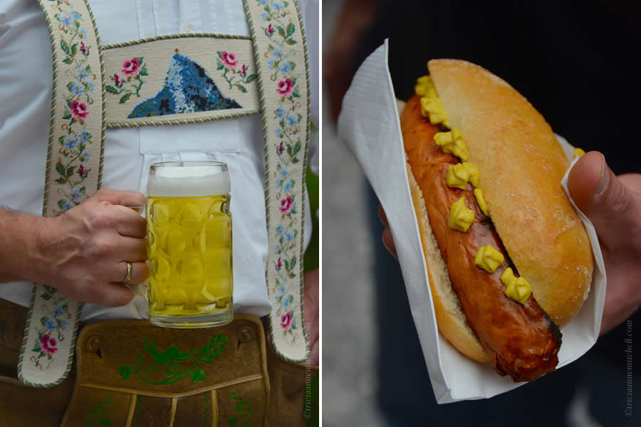 Two different pictures taken at an outdoor summer festival in Oberammergau, Germany. On the left, a man wearing embroidered suspenders holds a glass mug of a yellow beer. On the right, you can see the hand of a person holding a sandwich with Bratwurst, and dots of yellow mustard.
