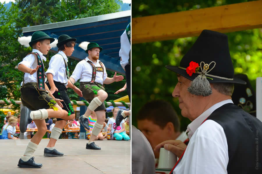 Two boys and an adult male perform a traditional dance in Oberammergau, Germany in the picture on the left. They are wearing green hats with a white feather. They appear to be slapping their feet, while lifting their knees. On the right, a close-up of a man wearing a Bavarian black hat, with grey tassels and a red flower.