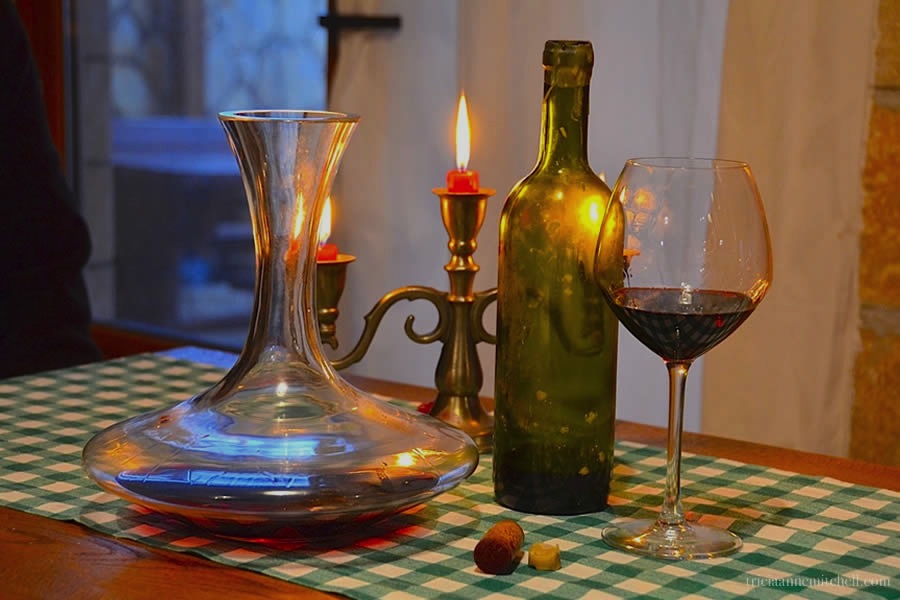 A bottle, decanter, and glass of red wine sit on a table with a candle.