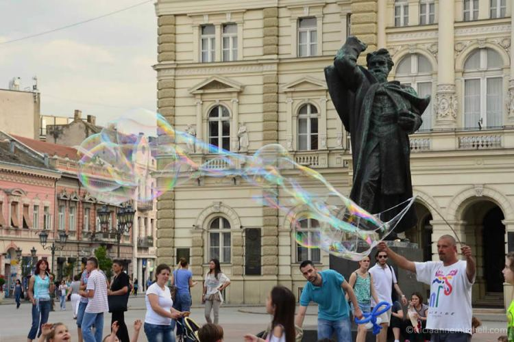A man creates giant soap bubbles, using a frame. He's overlooked by a statue in Novi Sad's main square.