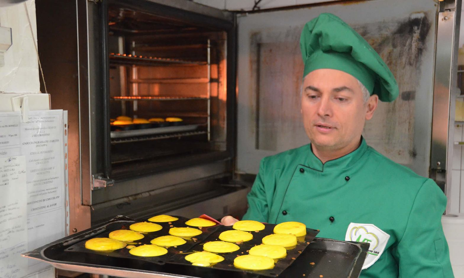 A chef, wearing a green hat and uniform, holds a tray of bright yellow souffles, preparing to put them in an oven.