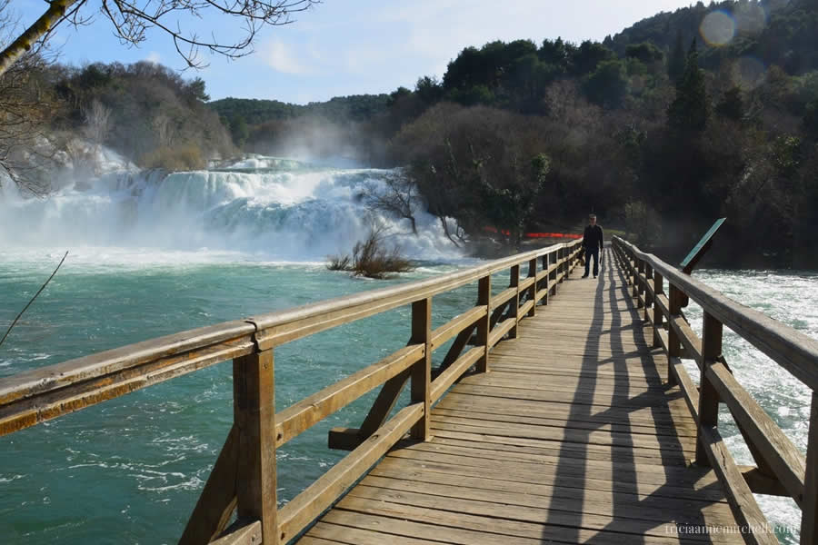 A man standing on a wooden bridge at Krka National Park in Croatia.