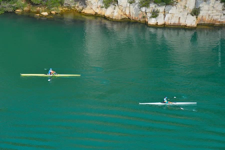 Two men row kayaks on the Krka River in Croatia.