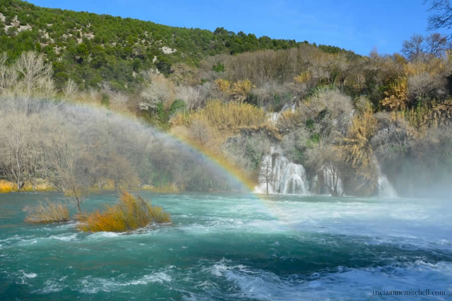 A rainbow over the blue water of Krka Waterfalls in Croatia