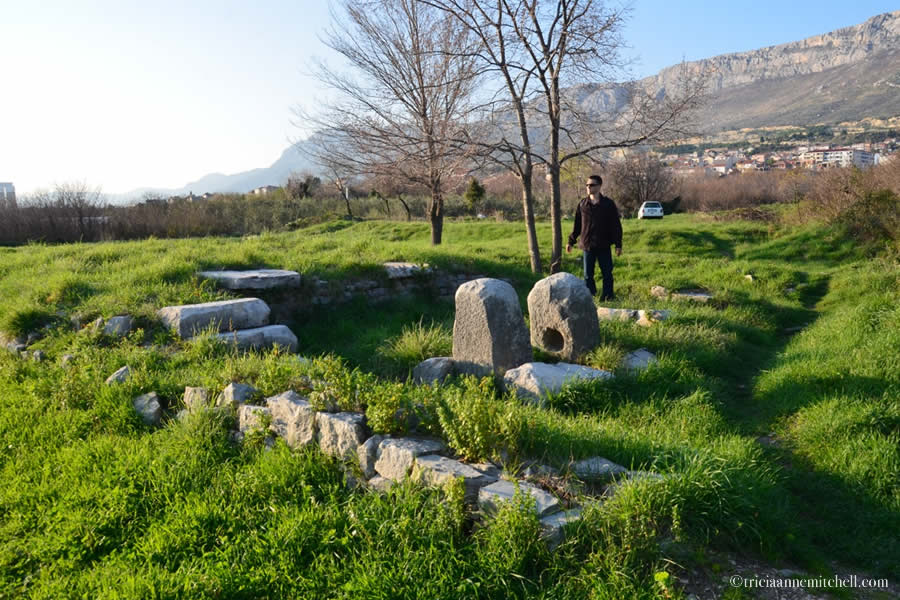 A male visitor stands in the ruined remains of ancient Salona's forum.