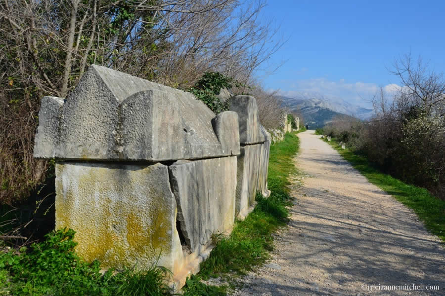 Two cracked sarcophagi line a crushed stone path in the Ancient Roman city of Salona, now present-day Croatia.