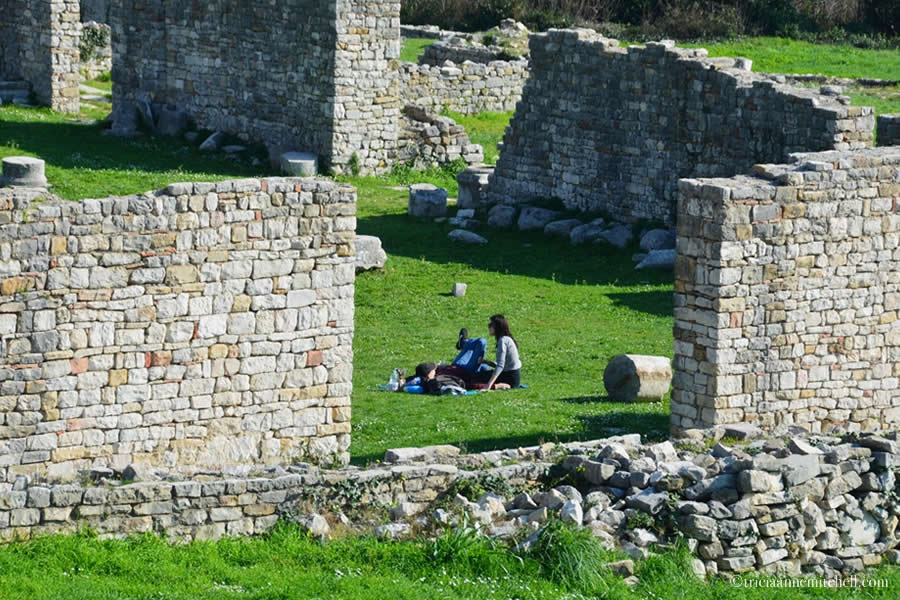 A couple lounges on the green lawn beside the ruined walls of the Ancient Roman city of Salona.