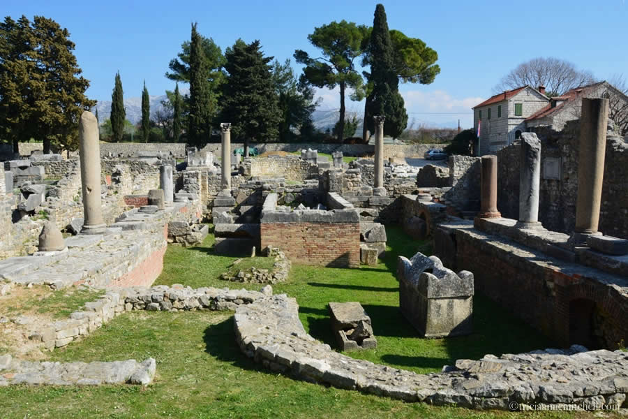 Ruined columns, capitals, walls, and cracked sarcophagi fill the lawn of Ancient Salona's Manastirine section.