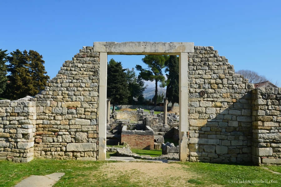 The Manastirine area is visible through the portal of ruined stone facade in the Ancient Roman city of Salona, now Croatia.