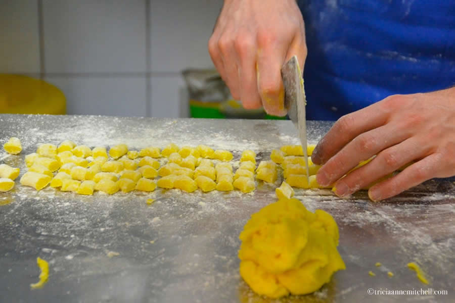 A male chef makes gluten-free gnocchi at a restaurant in Modena, Italy. Only his hands are visible.