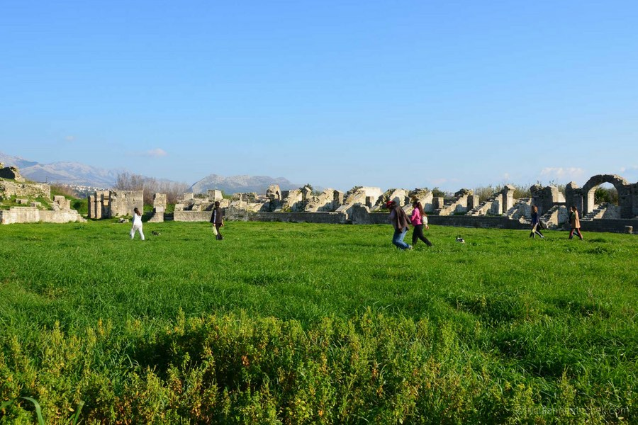 Several people walk through a grassy field, which is encircled by the ruins of Salona's ancient Roman amphitheater.