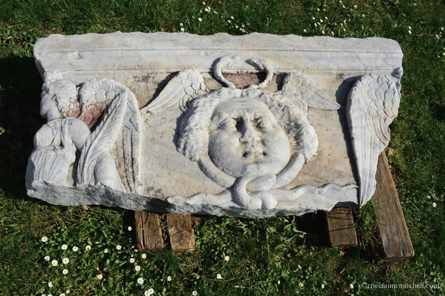 An ancient Roman marble fragment (with intricate carvings of a head and angel) sits on a wooden pallet in Salona's Manastirine.