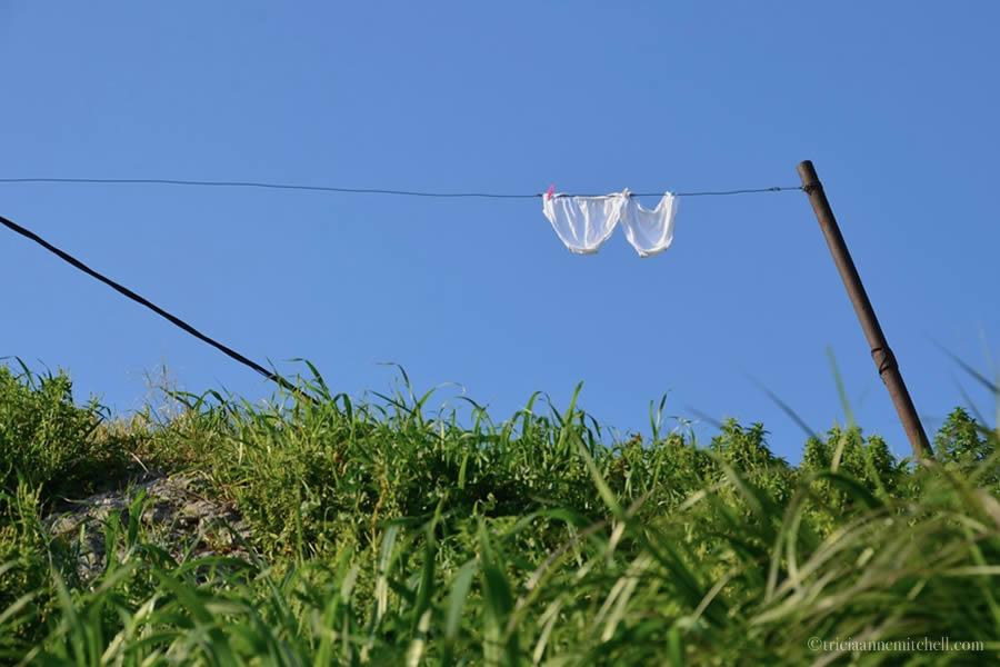 With a blue sky overhead, a pair of white underpants hang on a laundry line near the ancient city of Salona, Croatia.