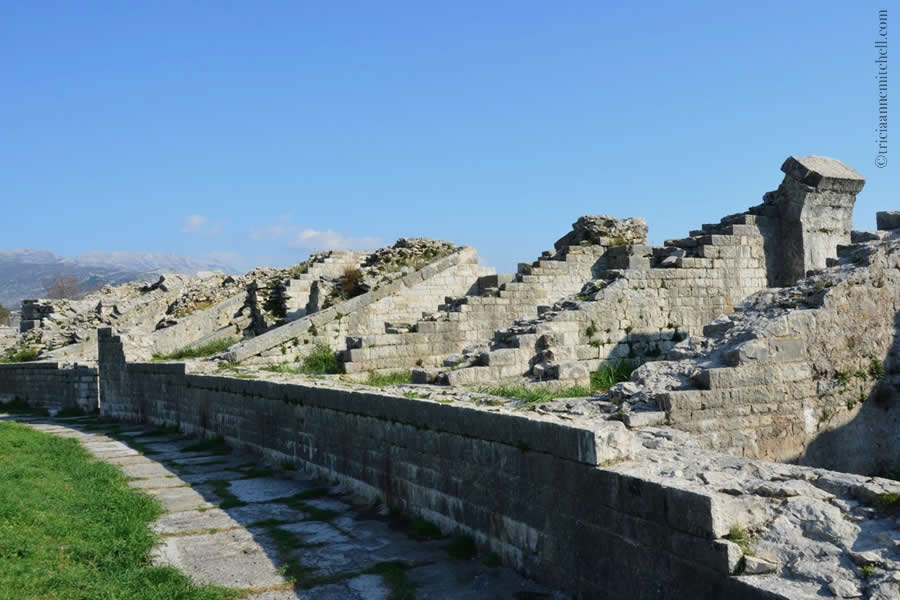 The ruined amphitheater remains of the ancient Roman city of Salona (now Solin, Croatia) are visible under a blue sky.