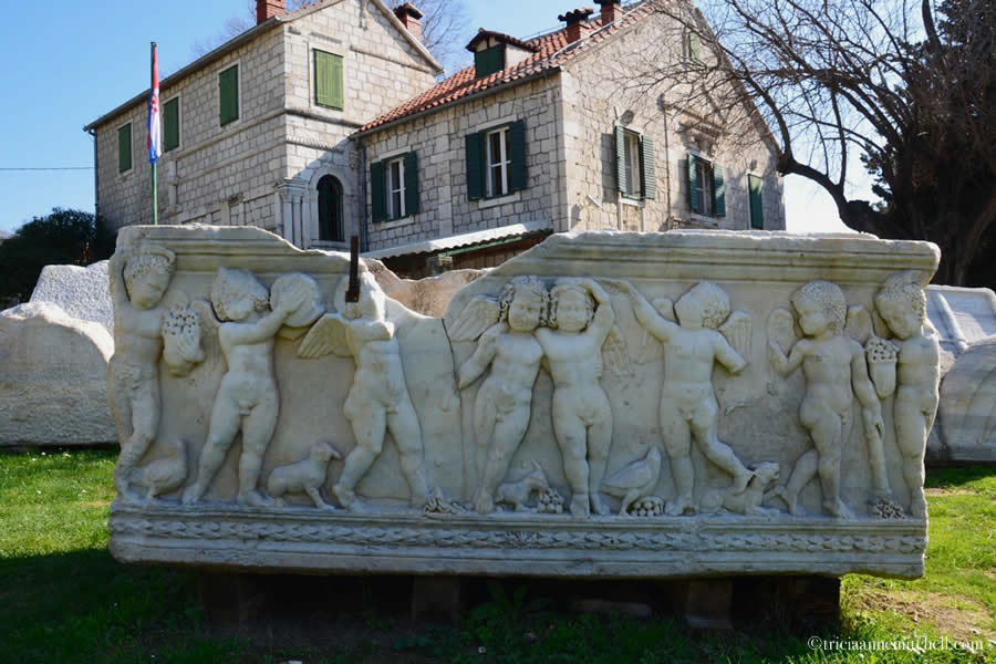A white marble sarcophagus decorated with cherubs sits on the lawn of the Manastirine in the Ancient Roman city of Salona.