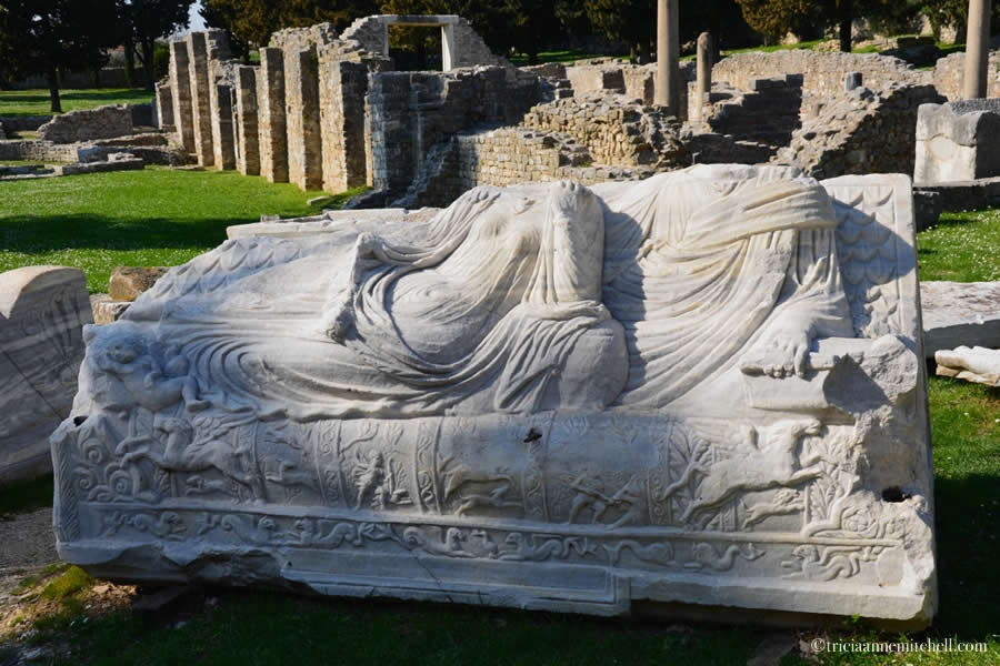 A fragment of a white marble Roman sarcophagus sits on the lawn, near a building's ruins, in historic Salona, Croatia.