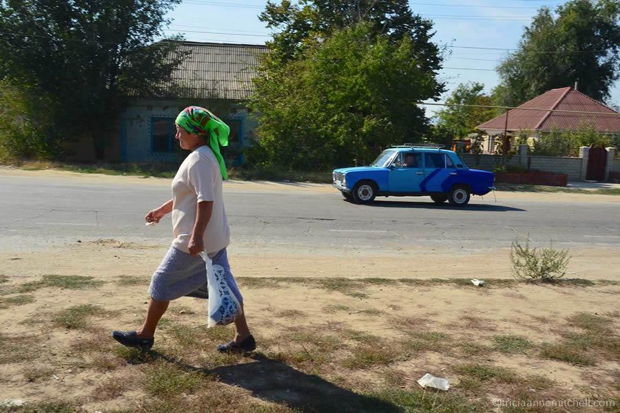 Woman walking on street in Moldova, alongside a blue car.