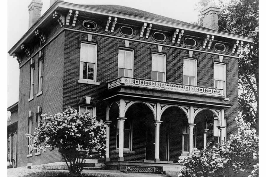 "A black and white photo of an Italianate style, brick home with an ornamental wooden portico, circa 1900. Known as the OJ Dimick House, there is a sign that says ""Union Mission"" rests atop the porch. This photo dates back to when the home was an orphanage."