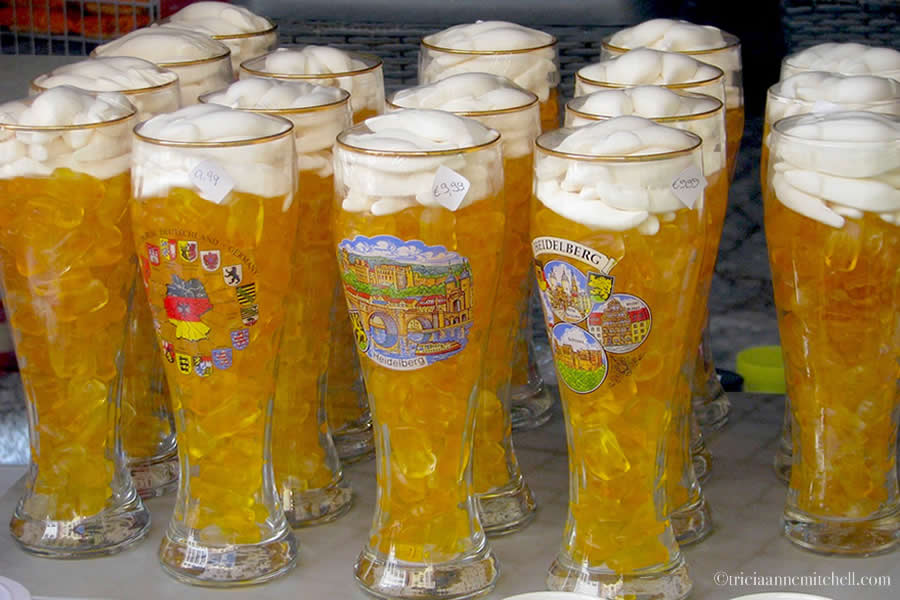 Yellow gummy bears are stuffed into a tall beer glass, resembling a glass of beer. They are for sale at the Gummy Bear Shop in Heidelberg (Gummi Bier)
