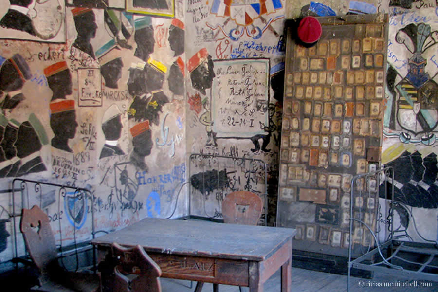 The interior of the Heidelberg Student Prison (Studentenkarzer) has painted walls with black silhouetted version of student inmates, along with old photographs, a desk, and chairs.