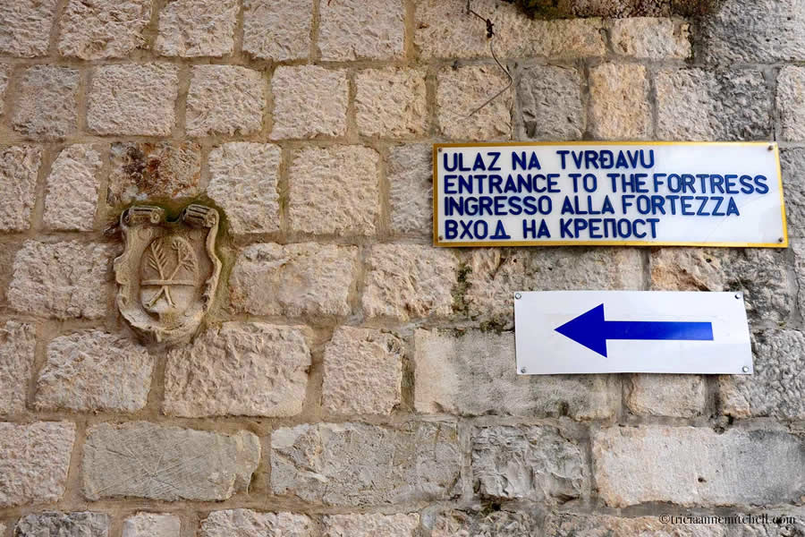 A sign featuring directions to the Kotor Fortress, written in 4 different languages.