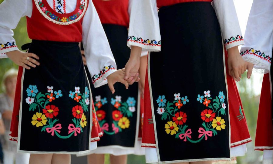 Female folk dancers - wearing traditional costume - hold hands in a Bulgarian village.