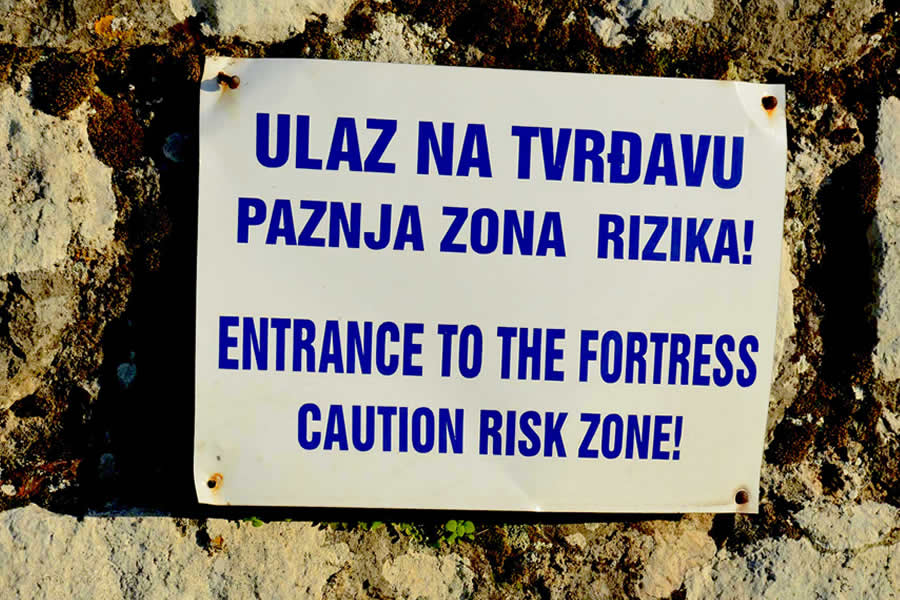 "A sign at the Kotor Fortress that reads: ""Entrance to the fortress. Caution risk zone!"""