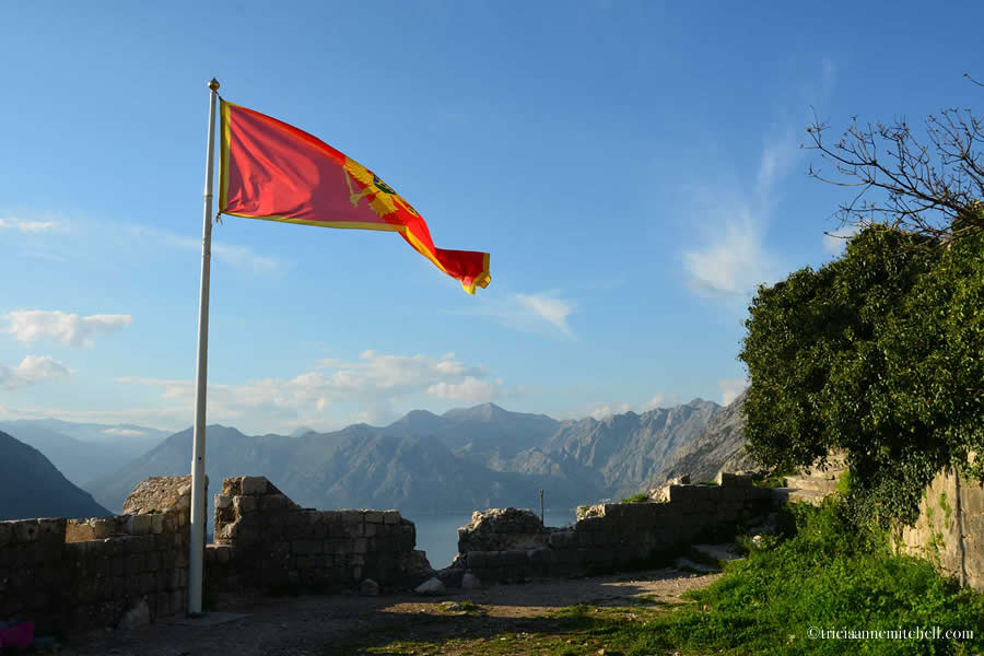 Montenegro's red flag blows in the breeze atop the Kotor Fortress, with views of the Bay of Kotor below.