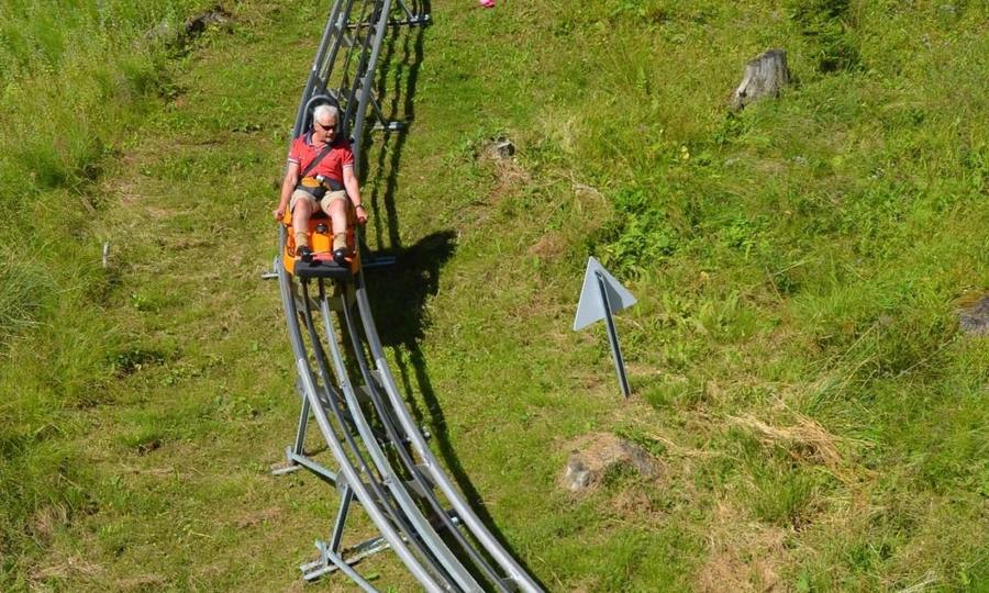 A man rides an alpine coaster on a green slope overlooking the village of Oberammergau, Germany.