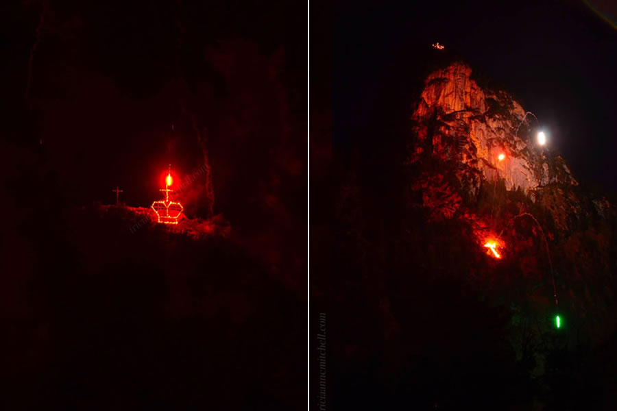 The Kofel, a mountain peak in Oberammergau, Germany, is illuminated with flares and flames. A symbol of a cross and royal crown are on fire. It is nighttime and the sky is dark. The event is an annual bonfire celebrating the eve of the birthday of the Bavarian King Ludwig II.