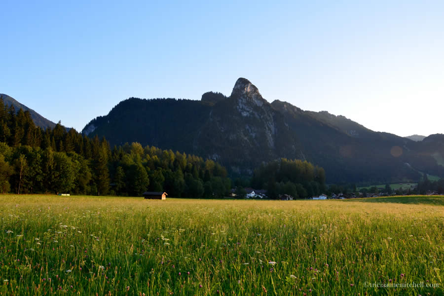 A pointed mountain towers over a yellow and green meadow in Oberammergau, Germany. You can see a small barn off in the distance.