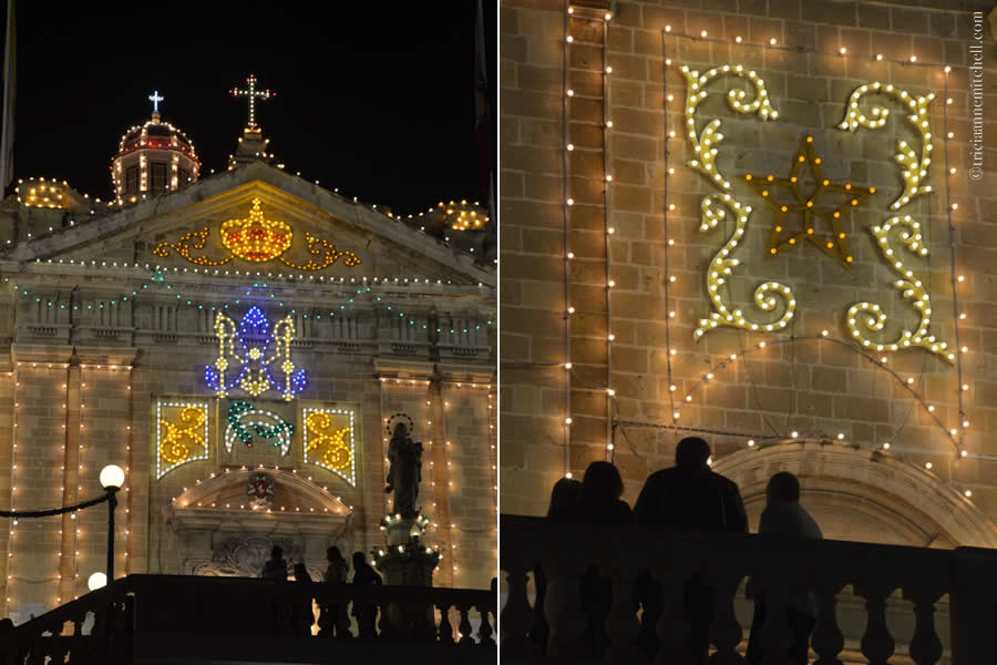 The silhouettes of people are visible against the colorfully-lit church celebrating the feast of the Immaculate Conception in Cospicua Bormla, Malta.