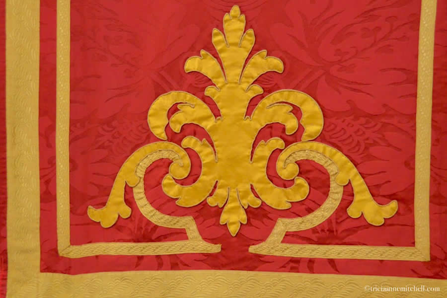 Red damask fabric with gold accents, decorating the interior of a Maltese church in Bormla / Cospicua for feast day celebrations.