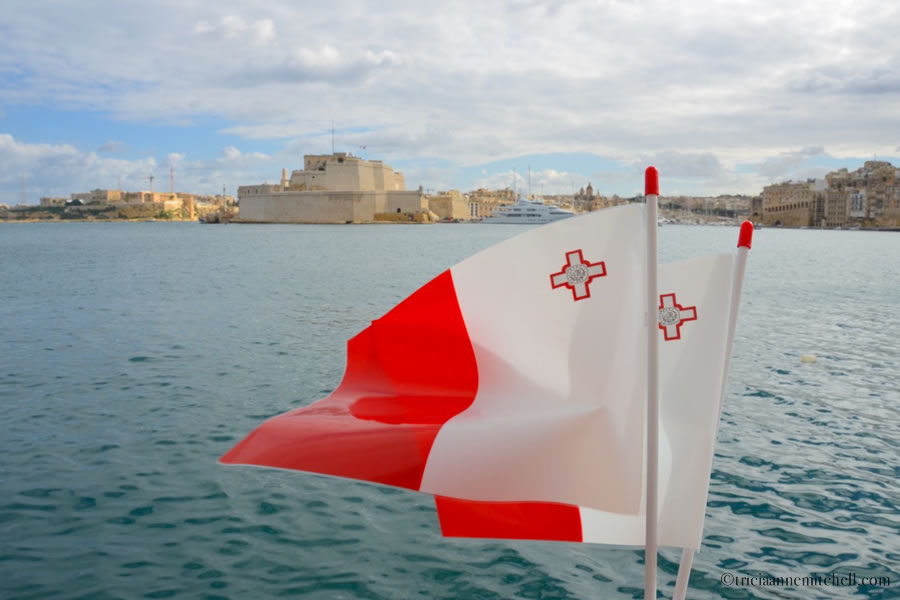 A pair of Maltese Flags blow in the breeze by Valletta's Grand Harbour and the Fort St. Angelo