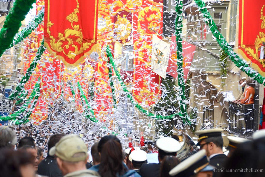 People march in a parade, under confetti, for St Paul Feast Day Celebrations in Valletta Malta