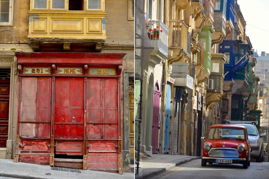 A vintage car drives on a steep Valletta street, past colorful and vintage storefronts.