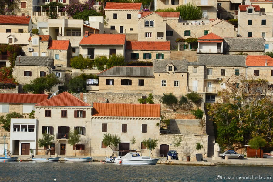 Limestone homes, with orange terracotta rooftops, line the water's edge in Pučišća, Croatia.