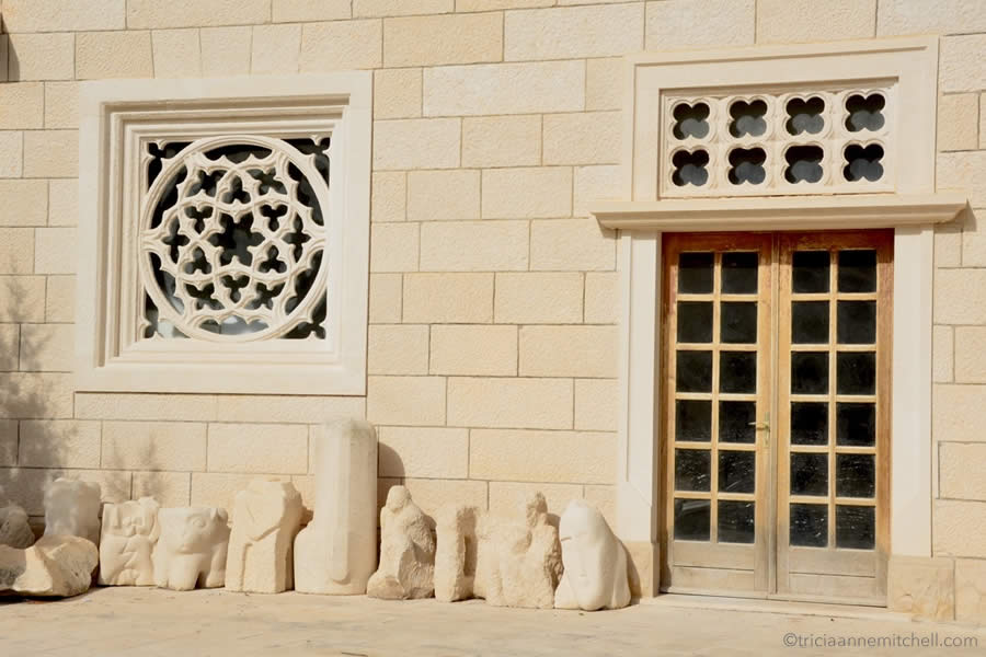 Limestone sculptures sit on the ground, beside an entrance to the Klesarska škola (Stonemason School) in Croatia, on the island of Brač.)