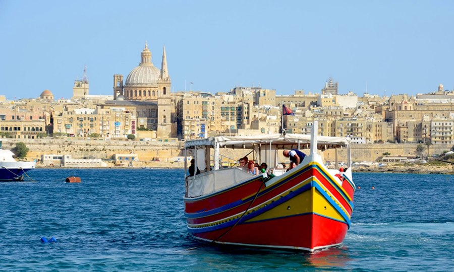 A multi-colored wooden fishing boats sits in the water, with the skyline of Valletta, Malta in the background.