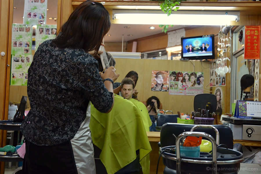 A woman cuts a man's hair at a salon in Bangkok.
