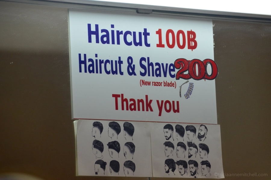 A price list for haircuts in Chiang Mai, Thailand, is posted on a barber shop wall.