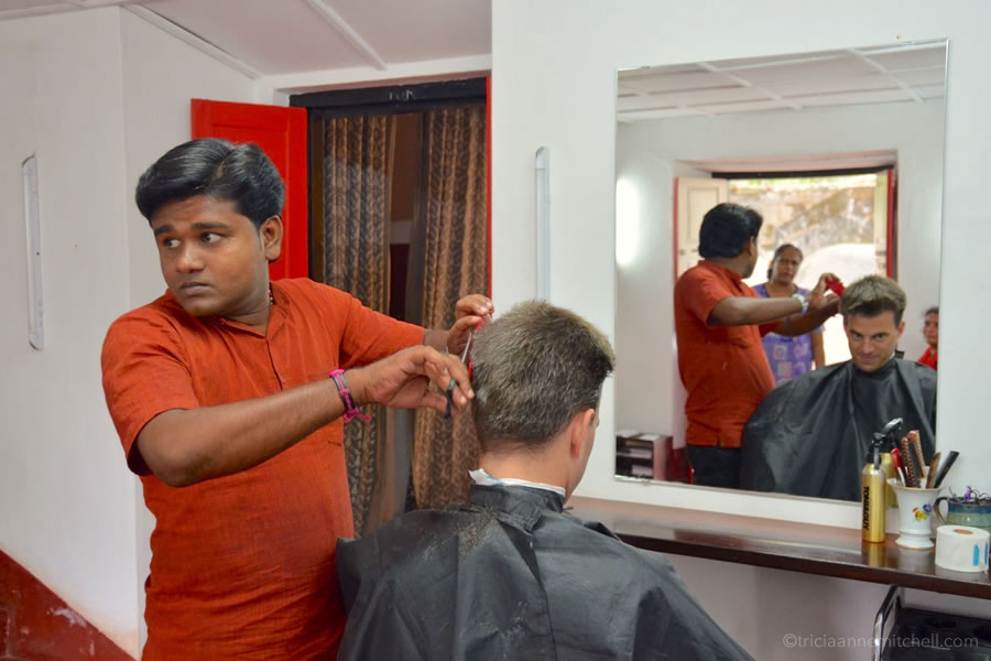 A man cuts a man's hair in Fort Kochi, India.