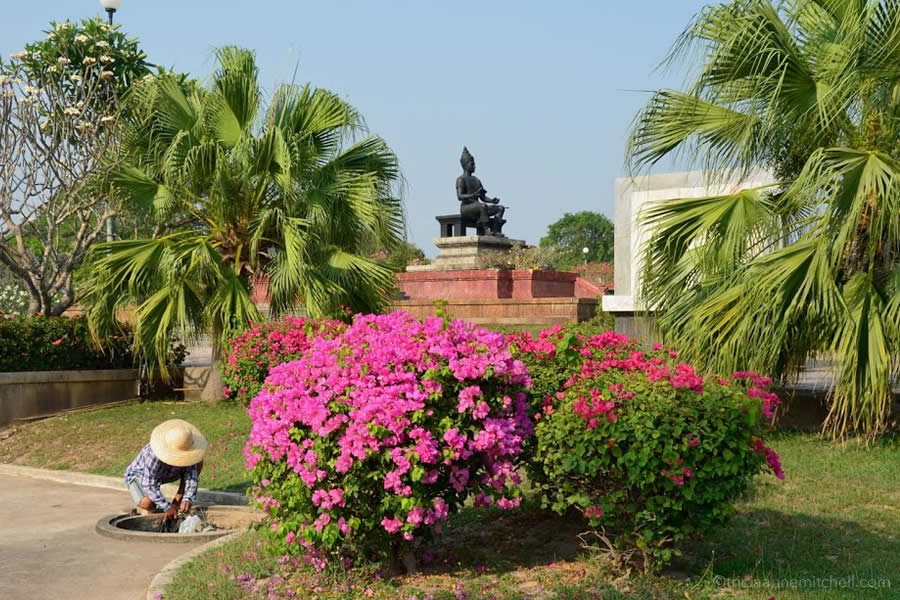 A gardener tends to the landscape around the King Ramkhamhaeng Monument in Sukhothai, Thailand.