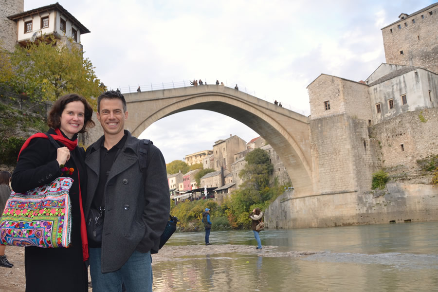A man and woman stand underneath the Mostar Bridge, in Bosnia-Herzegovina.