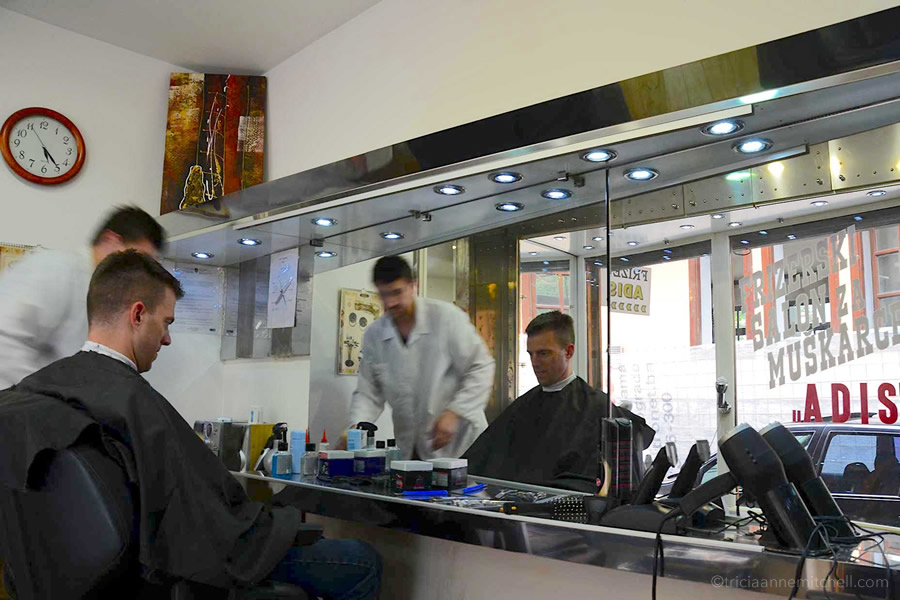 A man cuts a man's hair at a barber shop in Sarajevo, Bosnia-Herzegovina.