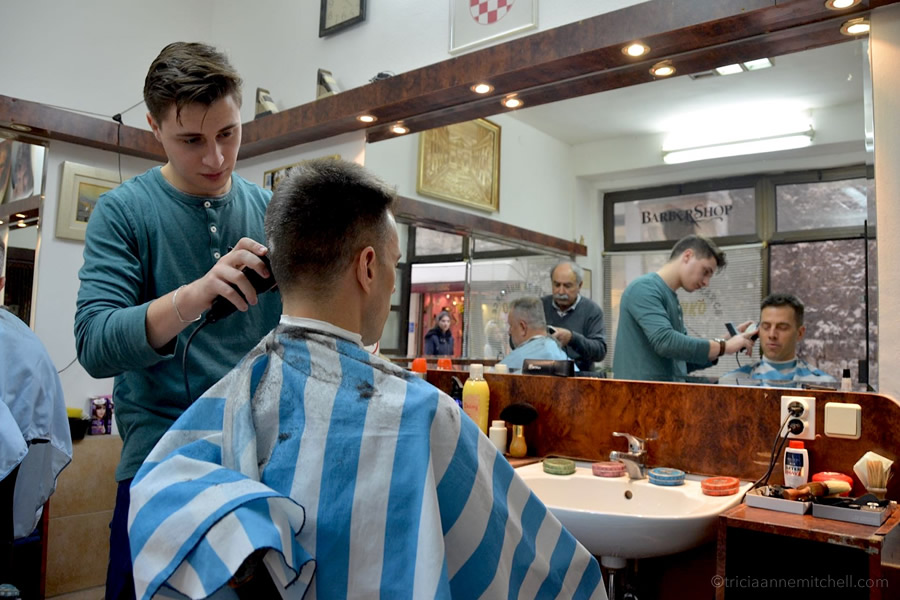 A man cuts a man's hair in a Split, Croatia barber shop.