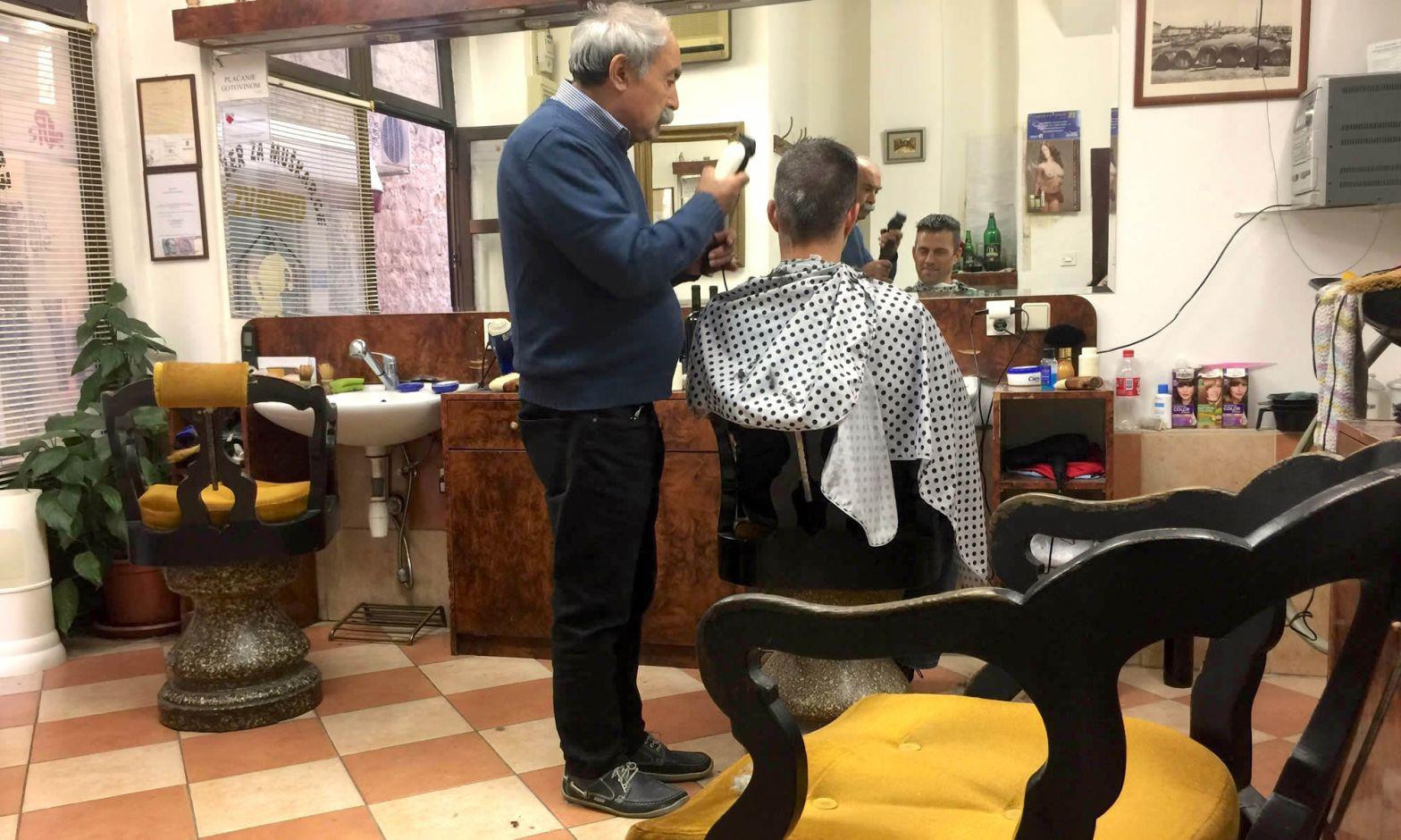 A man cuts a customer's hair at a barber shop in Split Croatia